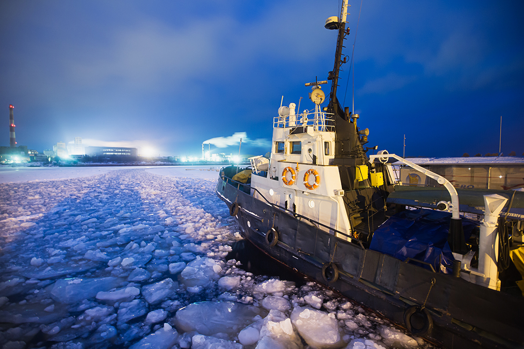 Boat travelling through ice towards town