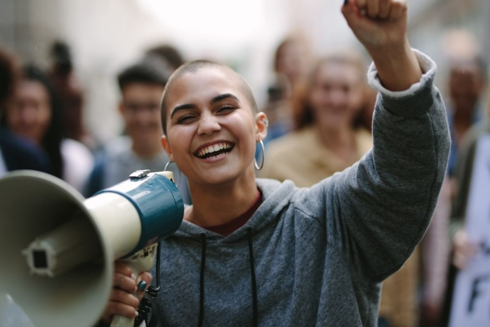 A woman with a megaphone leading a crowd of people.