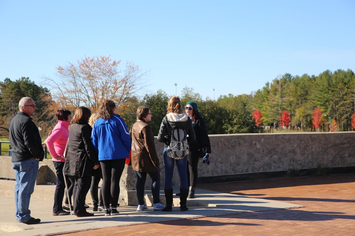 Students and parents outside on beautiful day taking a campus tour
