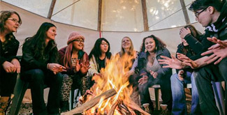 A group of students sitting around a fire inside a tipi.