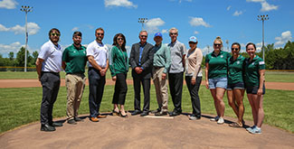 A group ofstaff, faculty and students standing on a baseball field mound