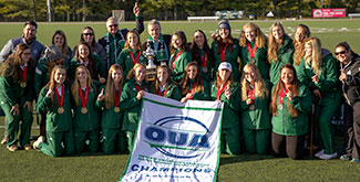 The Trent Excalibur rowers posing as a group on the field with the OUA banner