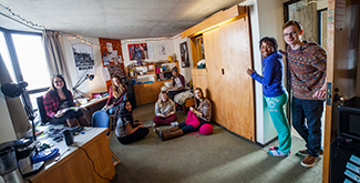 A group of students sitting in their dorm room at Trent University, smiling at the camera