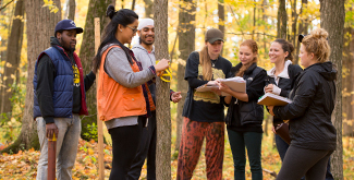 5 Students standing in the woods taking measurements of trees during a class activity