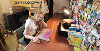 Student sitting at her desk in her dorm room typing on her computer, smiling at the camera