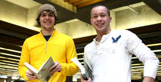 2 Students holding books in the library, main floor smiling at the camera