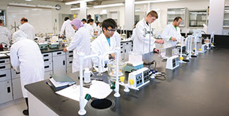 Students in white labcoats wokring in a chemisrty lab