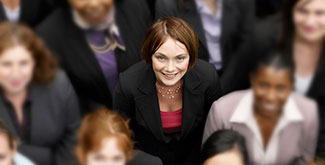 A woman in a business suit smiling up at the camera, surround by other people in suits that are blurred out