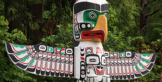 The opv of an indigenous totem pole outside in the summertime set against a wall of evergreen trees