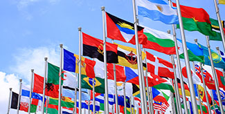 Many world flags waving in the air against a blue sky