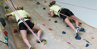 2 Students climbing the wall at the Athletic's Center with harnesses on