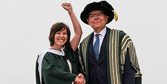 Student in her convocation gown on the podium during convocation shaking hands with Dr. Don Tapscott