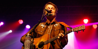Blue Rodeo lead singer performing on stage with lights behind him