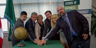 Staff, faculty and students pushing a button on a green table with a globe