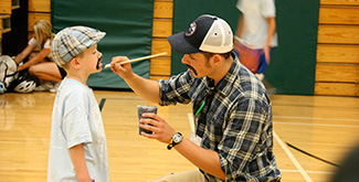 A student face painting on a young boy in the gymnasium