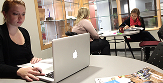Student on a macintosh laptop studying in a common area with other students studying at tables behind her