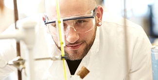 Student in a lab coat with goggles on looking at a testtube in a science lab