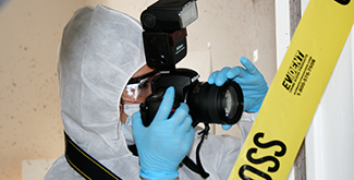 Student in white coveralls with hood using a camera to photograph a crime scene