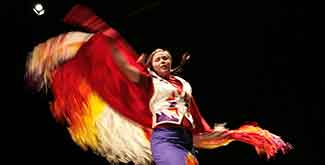 INdigenous student dancing on stage against a black backdrop