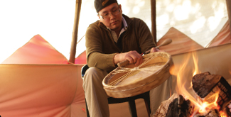Indigenous student sitting on a chair in a teepee stringing a drum near a wood fire