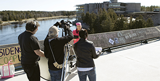 3 Journalism students on the Faryon bridge filming an interview with an indigenous student using a large video camera