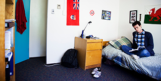 A student sitting on his bed in his Otonabee College dorm room reading a book