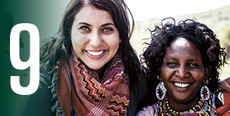 2 women smiling at the camera in a third-world country wearing brightly coloured scarves
