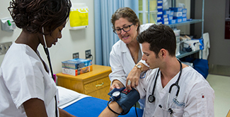A female student taking the blood pressure of a male student as the teacher interacts with them teaching