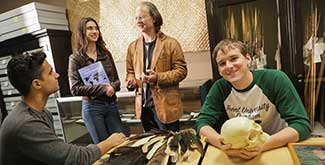 3 students sitting around a table, while one talks to a professor in a leather jacket, while one holds a skull and smiles at the camera