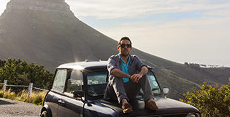 Male student in casual clothes sitting on the hood of an old car on the side of a road with a mountain behind him