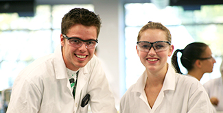 A male and female student, standing at a workbench wearing goggles and white lab coats, smiling at the camera