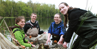 4 students in a river, wearing waders, looking at river samples in a net