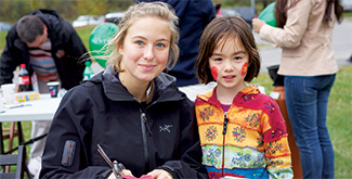 A female student sitting beside a young girl with face paint, in their fall jackets, behind a craft table