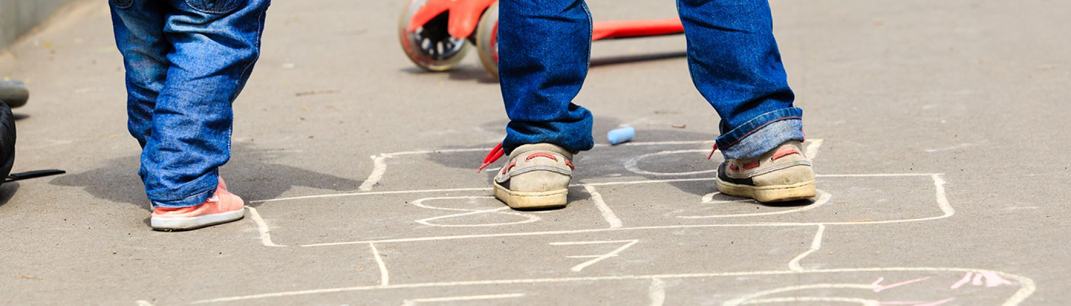 2 young children playing hopscotch on the concrete in a playground