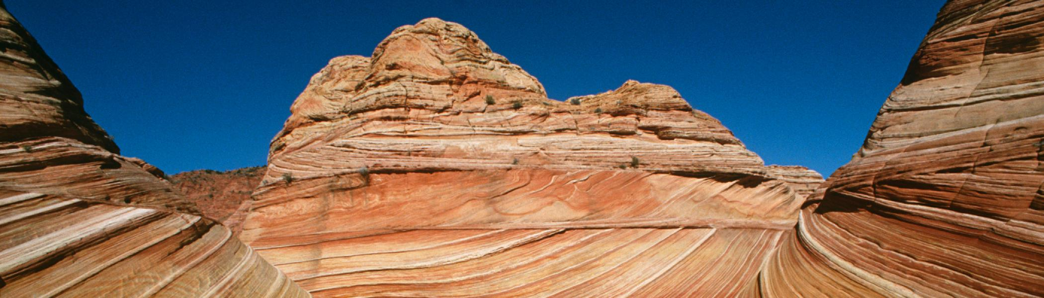 Brown rock formations in the desert against a blue sky
