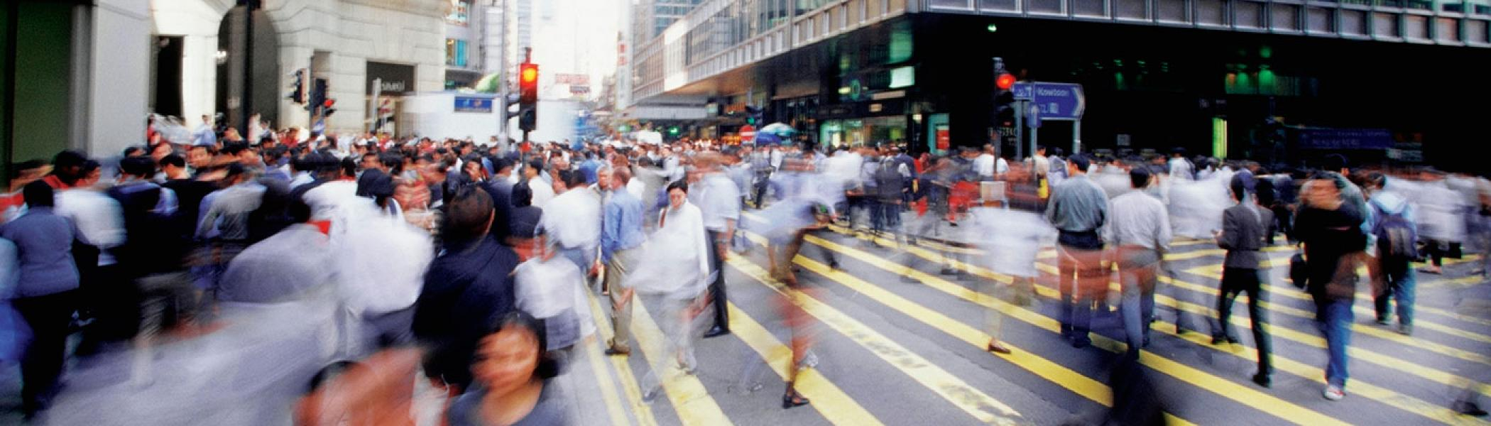People walking across a busy street, out of focus