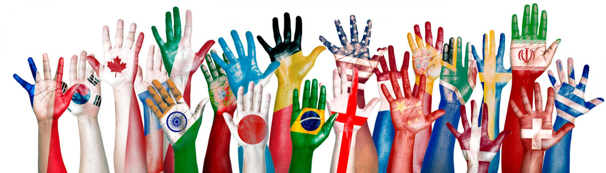 Hands painted with flags of the world reaching up.