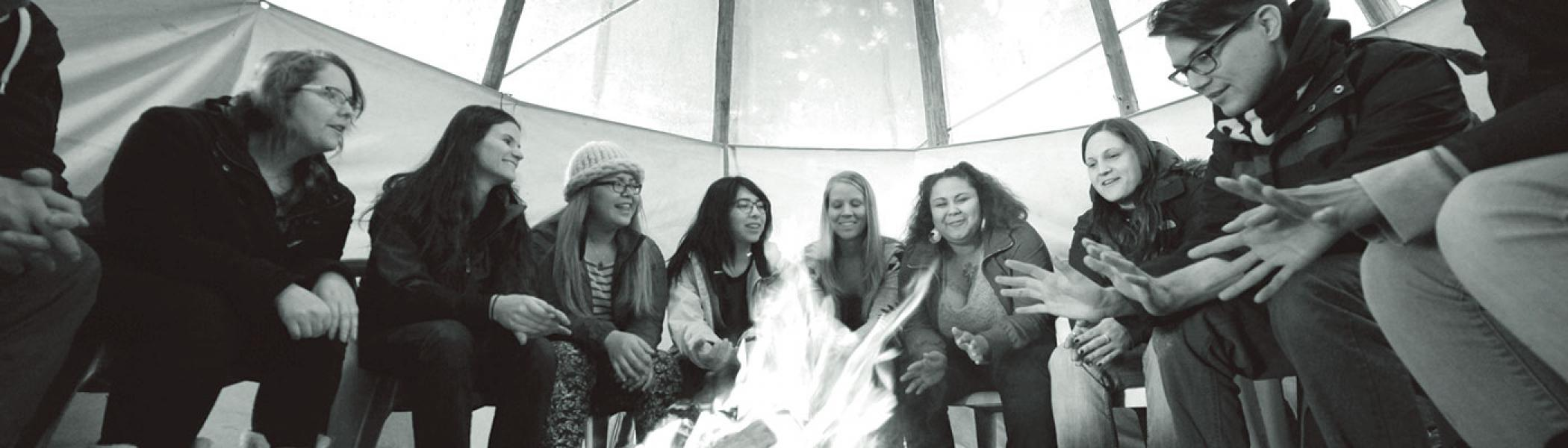 A group of students gathered in a tipi around a fire for class in the late fall