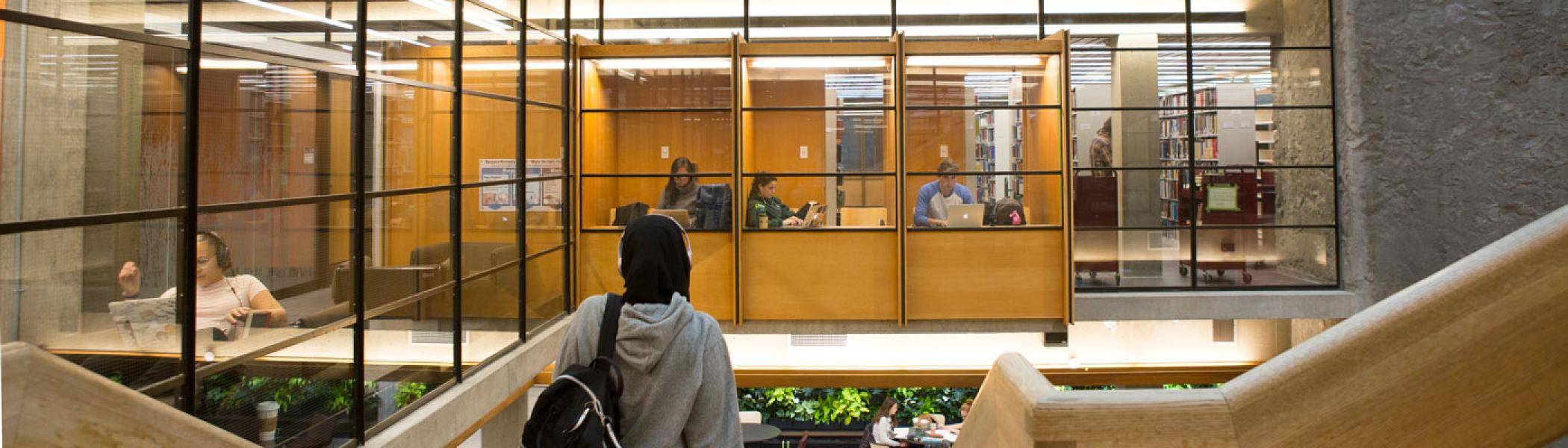 View from the top of the stairs at Bata library showing students working in study carols