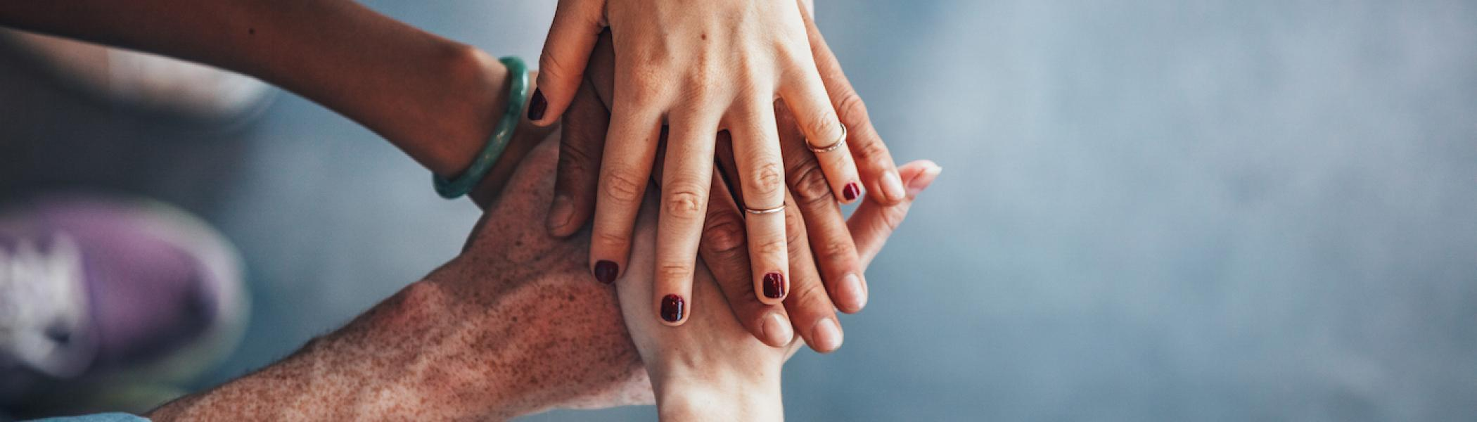 Hands stacked on top of each other.