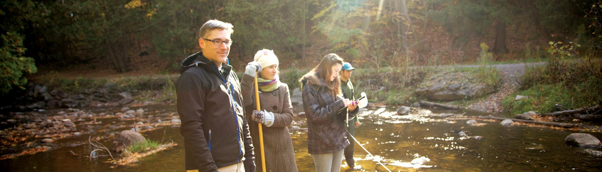 Professor and 3 students standing in a river on a sunny morning gathering samples