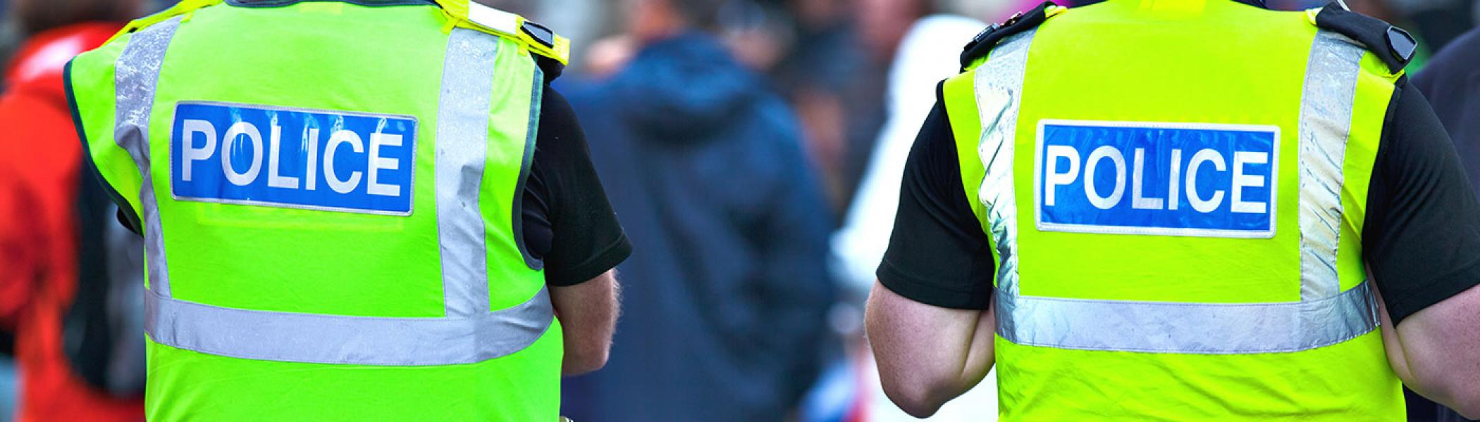 Two members of the police stand next to a crowd whilst wearing green high-vis vests.