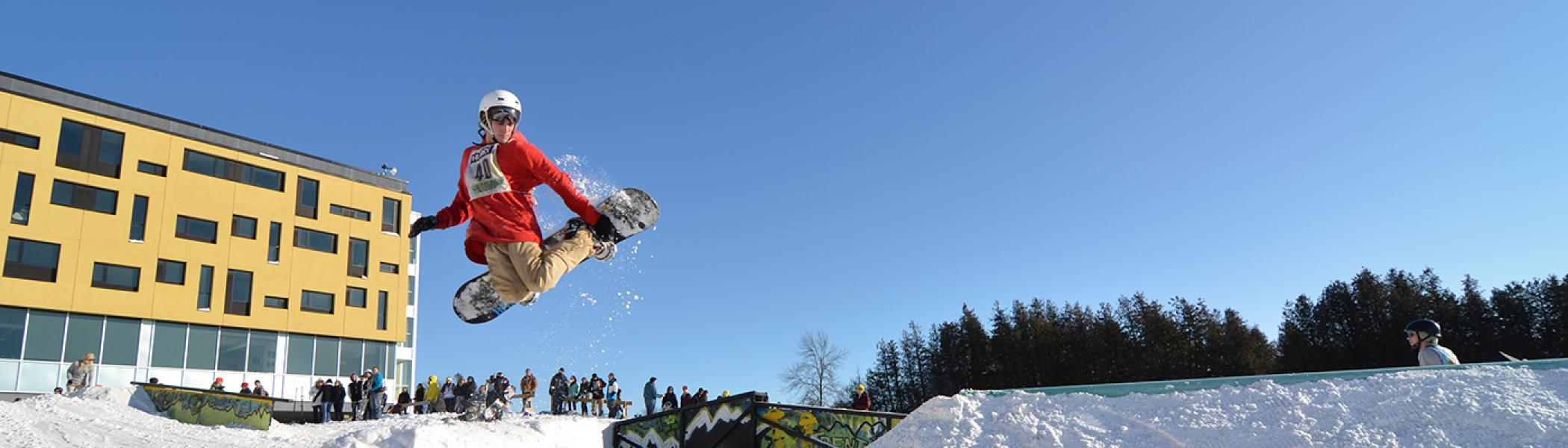 Student performing a snowboard air trick during railjam in the witer time