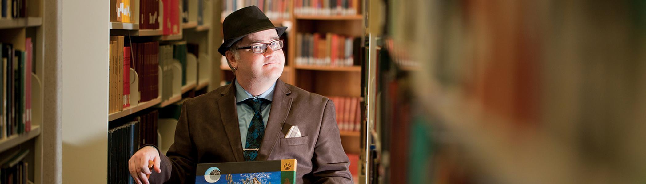 PhD Student Derek Newman-Stille sitting in the library amongst the bookshelves holding his book