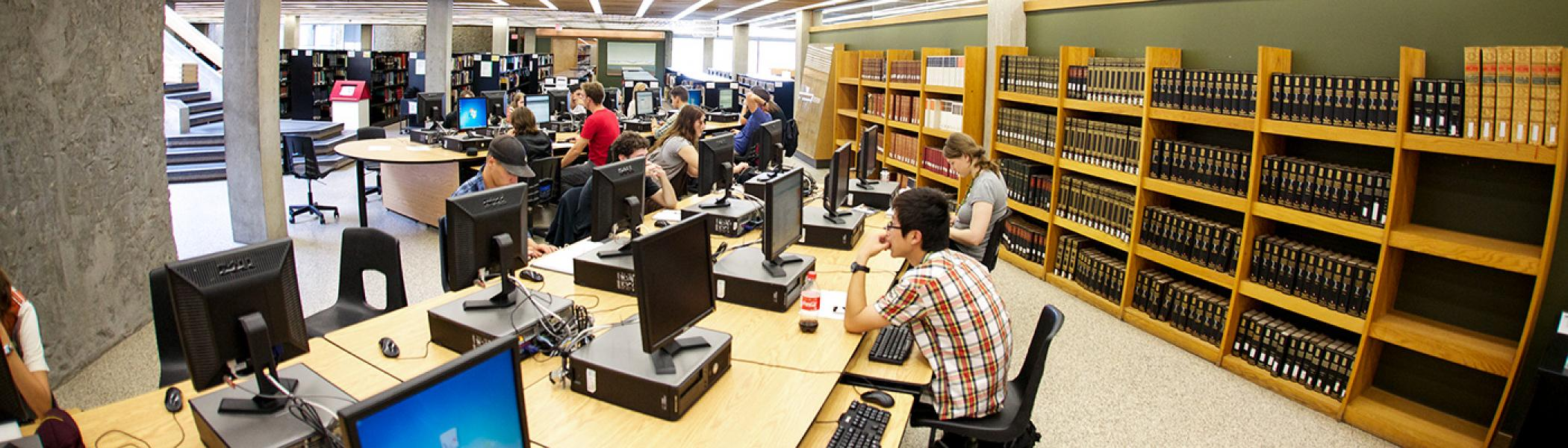 Students sitting at computers studying in the library surrounded by book shelves