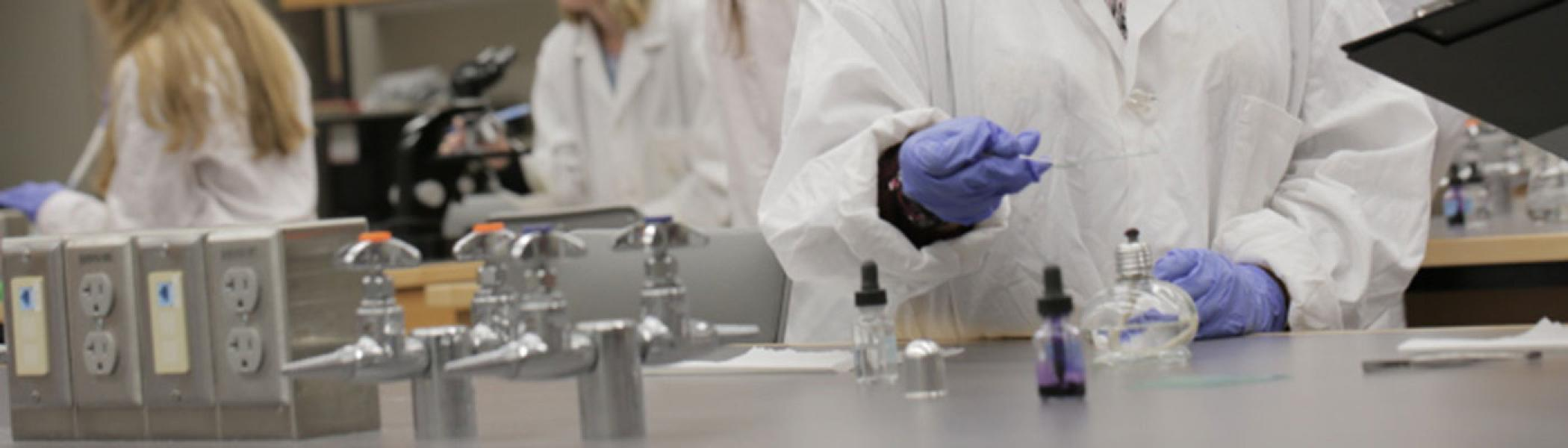 A student in Instrumental Chemical Analysis working in a lab