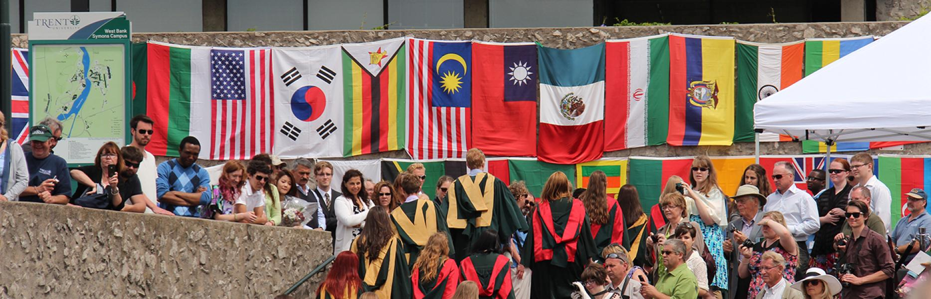Convocation at Trent with many flags from around the world hanging