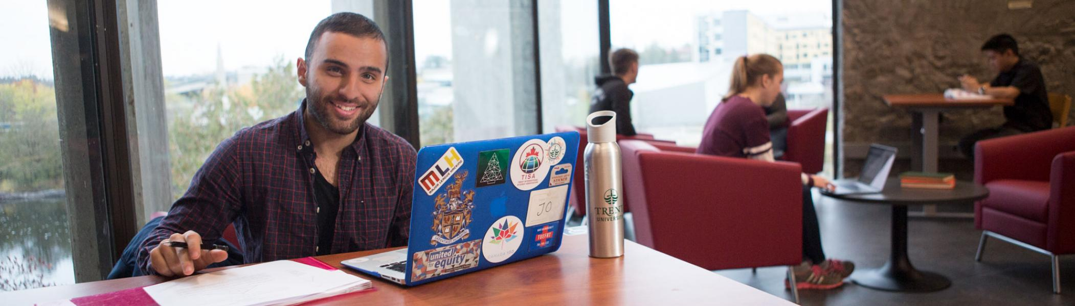 Trent University student sitting at a desk with a laptop in Bata library