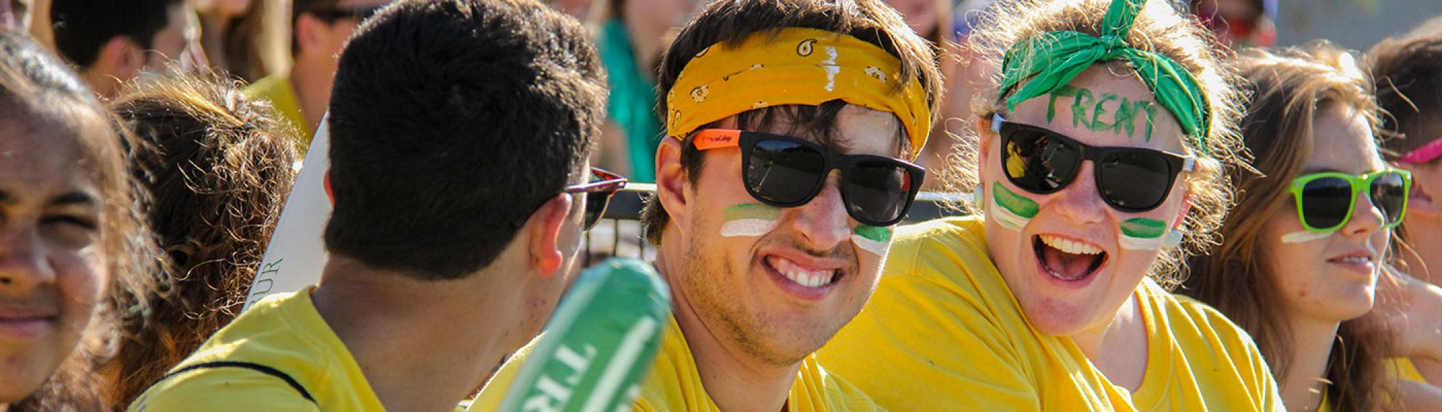 2 Students sitting in a crowd of students smiling at the camera during introductory seminar week, wearing sunglasses and face paint