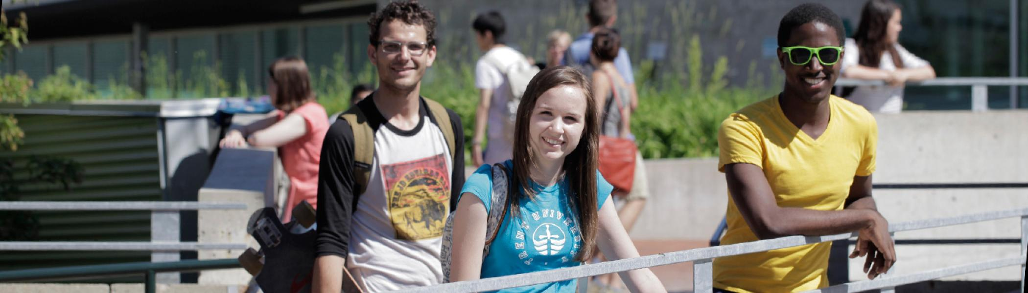 Students standing at the railing of faryon bridge near gzowski college in the early afternnon